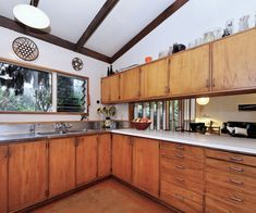 Wood kitchen drawers, stainless steel bench: mid century Titirangi house by Kelvin Grant