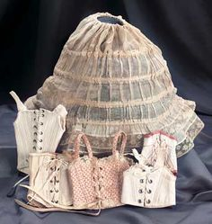 """Early Muslin Hoop and Five Corsets 10"""". The muslin hoop has an adjustable drawstring waist,and four graduated width hoop rings,with two borders of lace edging at the hem. Along with five various corsets,three with narrow waists specifically for lady dolls,and each with original grommet holes and lacing. Mid- 19th century."""