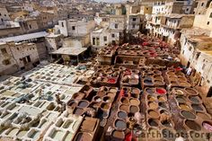 Fes, Morocco. The process of turning animal hides into soft colorful leather has remained unchanged since medieval times. Amongst other things, those vats contain pigeon excrement and cow urine.