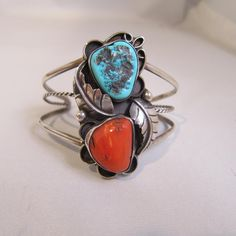 A beautiful Native American - probably Navajo sterling silver split shank cuff bracelet with bezel set turquoise and coral. Has nice antiquing around the edges, feather and rain drop details. The top measures 2 long. It is in great condition. Would fit wrist size 6-7 the best. It weighs 23.10 grams. It is signed RS, but cannot find the maker. Not marked sterling, but tested positive. Do not use liquid polisher on this cuff. It can hurt the stones and it will also take away the antiquing…
