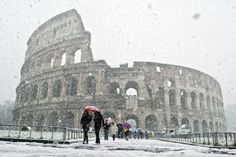 People walk outside Rome's ancient Colosseum during a snow fall.