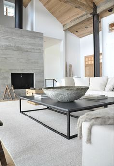 A modern rustic North Carolina living room designed by Briggs Edward Solomon...  concrete fireplace, wood plank ceiling, streamlined coffee table