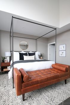 A modern master bedroom in the city of Chicago. Gray walls, white bedding, and a 4 post bed. Absolutely adore this space! Plus the brown leather bench at the foot of the bed really ties the entire space together.