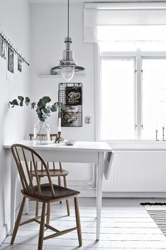 I like the look of this small dinning area in this all white kitchen. By adding a lamp right above the table, a string for picture and a little shelf, a separate area in the room is created. The woode