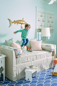 In 4-year-old Hudson's room, a sandy-hued linen daybed from Pottery Barn goes from neutral to knockout when paired with bolsters and Roman shades in Katie Ridder Beetlecat fabric, orange and green patterned throw pillows, and a vintage brass marlin from E