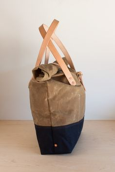 Made from waxed cotton canvas and Hermann Oak natural veg-tan leather. Two…