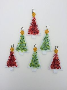 These colourful and fun fused glass Christmas trees in red and green would make a striking addition to your Christmas tree. The tree decorations have been hand cut, assembled and fired in my kiln at home. I have cut white Christmas tree shapes and scattered them with small shards of glass in shades of red and green and contour fused them for a very tactile ornament. These unusual tree ornaments measure 8.5cm high and 4.5cm wide and come in a set of six. They would make a unique addition to…