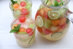 ~3 cups of mixed melon balls (watermelon, cantaloupe, honeydew)  2-4 tablespoons of honey, adjust to taste  1 lime, juiced  ¼ cup to ½ cup of grappa, adjust to taste – can also use pisco or a clear grape brandy  1 bottle of moscato wine, chilled  ~ 1 ½ cups of sparkling water, chilled   To serve and garnish:  Mint leaves  Lime slices  Ice cubes or frozen melon ball ice cubes