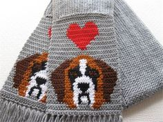 St. Bernard scarf. This handmadegray scarf is part of my love my dog scarf series. Scarf is made with a very soft acrylic yarn, and features a St Bernard and red heart on each end. The scarf is loom knit (double thickness) with gray and then I crochet the sides of the scarf and dogs into the ends. The Saint Bernard dogs are crocheted with rust, black, white and brown.   This is a very well made scarf and all loose ends are sewn in. The last photograph shows the back of the scarf.   Scarf…