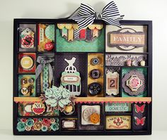 gorgeous shadowbox - I love the section filled with rolled paper flowers.