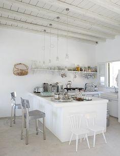 cocina abierta con amplia isla prolongación de la encimera, baldas en lugar de muebles altos, suelo de microcemento y lamparas colgantes de estilo industrial