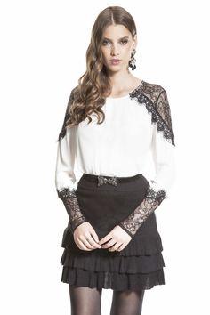 Blusa de crepe de chine com recortes em renda nos ombros e nas mangas, saia preta de tricô com babados, cinto regulável de camurça com fivela de tigrinho.