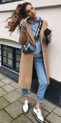 Negin Mirsalehi + beige overcoat + pale blue hoodie + jeans combo + spring style + black-soled white brogues + funky cross body mini bag.  Brands not specified.
