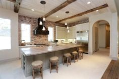 pale gray kitchen cabinets; exposed brick backsplash; reclaimed wood island counter