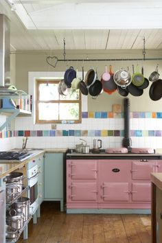 Colorful kitchen with vintage pink oven and an array of colorful accent ceramic tiles