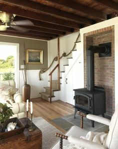 The other side of the living room reveals a fabulous wood burning stove and a glimpse of the rope staircase to the upstairs bedroom. Via Completely Coastal Inspired Living (the only thing we caution is that both sides of the staircase need a rail for safety)