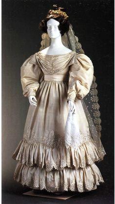 1830 - 1830  Robe de mariée en taffetas champagne à décolleté bateau, corsage à collet en pointe drapé devant et derrière, manches gigot plissées aux poignets, manchettes brodées. Jupe ronde froncée à deux larges volants festonnés, longueur aux chevilles. Le corsage et les manchettes sont brodés de guirlandes de fleurettes. Les motifs brodés sur la jupe et les volants - fougères ou palmes et branches fleuries - rappellent les motifs à la mode de l'époque.  Bruxelles