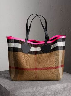 A supersized reversible tote from Burberry in supple leather bonded to Canvas check. Neon sealed seams add a clash of colour to the unisex bag.