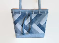 This large denim blue jean tote bag, shoulder bag, handbag or purse was constructed from a variety and shades of upcycled recycled denim blue jeans and repurposed cotton fabric. This bag is spacious and durable, a perfect size to comfortably carry your daily must have items, magazines, books and miscellaneous items. The unique exterior front and back of this bag was constructed from a variety of colors and shades of upcycled recycled denim blue jeans. The denim pieces of the main exterior…