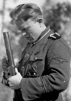 """SS Gebirgsjäger Regiment 11 """"Reinhard Heydrich"""". Cleaning out part of his weapon. *note the wounded in combat medal on his left breast pocket."""