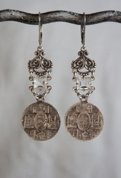 """Matching vintage Italian religious medals hang from genuine art deco crystal connectors from an old necklace. They connect to aged sterling plated ornate jewelry connectors. Sterling silver ear wires finish off the pair. Length: 1 5/8"""" from bottom of ear wires. —by French Feather Designs"""