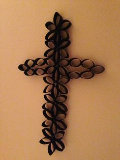 Cross made from paper towel rolls.  Slightly flatten  paper towel rolls and cut into 1 inch pieces. Arrange pieces into shape using repeating pattern. Hot glue touch points together. Spray paint.