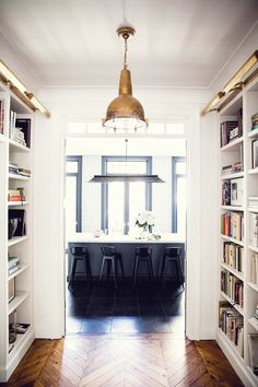 Built in bookcase hallway + copper lighting and black kitchen details