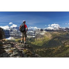 Male hiker standing on top of mountain ridge overlooking snow peaked mountains and forest valley below with blue sky and clouds Waterton Alberta Canada Canvas Art - Michael Interisano Design Pics (19
