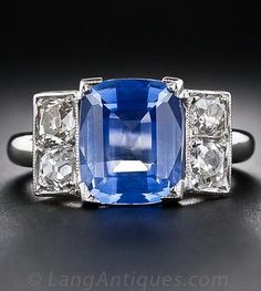 A stunning and sophisticated original Art Deco ring, crafted in platinum, circa 1930, and featuring a bright cornflower blue Ceylon sapphire weighing just under four carats. The colorful gemstone is guarded left and right by a pair of glistening old-mine cushion-cut diamonds, all four weighing .60 carats total.