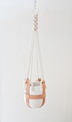 leather sling plant hanger with traditional macrame knots.
