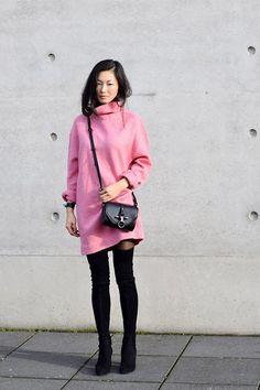 Модель с розовом платье-туника с высоким воротом и черные сапоги-чулки