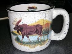 These white with black speckles trail mug are decorated with the Scenic Moose artwork, original Painting by Dann Jacobus. Decorated by hand in the U. Product is Dishwasher and Microwave Safe. Rustic Mugs, Mug Shots, Microwave, Moose, Dishwasher, Trail, Original Paintings, Display, The Originals