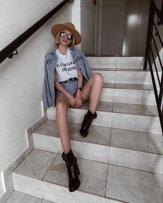 chapéu fedora camel, t-shirt branca com frase, jaqueta jeans oversized, short jeans vintage, bota salto tratorado, cinto western.