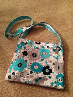 Floral print cross body purse with two outside pockets and a magnetic clasp center pouch