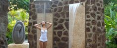 A woman standing under the spa rain shower