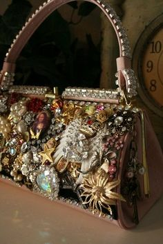 vintage jewelry brooches on handbag--holy moly--I don't think I'd lug this around but maybe use it for a flower arrangement--looks like something you drag out for an old lady tea party-ha