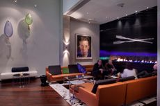 Fireplace bar area with intricately designed glass oars by Brent Kee Young and an original Chuck Close piece.