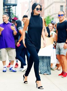 Selena Gomez wears a black high-neck tank top, skinny jeans, black sandals, and Dior sunglasses