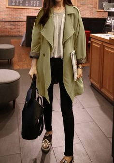 This slouchy army green coat features a pair of long sleeves with rolled up cuffs and is designed with two front pockets and a button closure at the front.