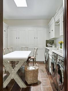 Laundry room with x leg table for folding, custom cabinets with two washers and two dryers   laundry-room-laundry-room-features-custom-x-leg-table-for-folding-custom-cabinets-farmhouse-sink-and-2-washers-2-dryers The Refined Group.