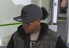 """Bank robbery suspect: described as a black male with curly dark hair, a ponytail or """"bun"""", approximately 5-7"""", medium to chubby build, glasses with black frames, brown eyes. He wore baggy clothes, black gloves, a black hooded jacket, and a baseball cap. Info? Call police at 613-236-1222 x 5116 or Crime Stoppers at  1-800-222-8477 (TIPS),"""