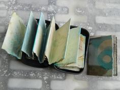 """May moon tiny journal. Tiny rust printed accordion journal in a tin with mica embellishments. 1 1/2 x 2 1/4""""."""