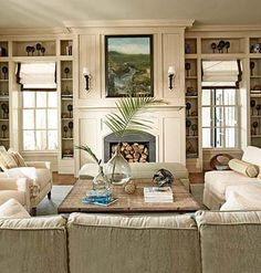 Fireplace flanked by shelving and an abundance of cream color