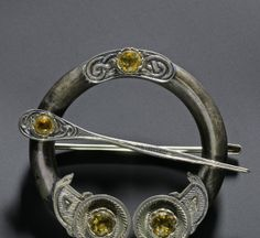 Penannular Celtic brooch set with yellow glass, the terminals decorated with engraved feather work, with a long hinged silver pin, by Ferguson and MacBean, Inverness