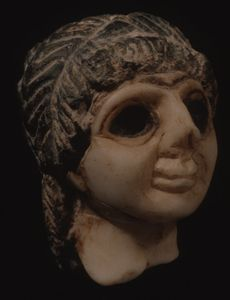 Marble Head of Female Orant with Black Hair Diyala Region, Sumer; 2600-2350 BC; 2.6 inches  The exquisite miniature, creme marble head of a woman came from an orant statuette. Her mouth with a subtle smile accents her straight nose, now broken at the tip. Cavernous, blackened eye sockets remain from bitumen adhesive where large eyes were once inset. Almost unique among orant figures, she has hair of a different stone, black serpentine.