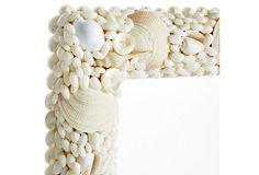 The perfect addition to a coastal home, this cream-colored wall mirror is adorned in a stunning arrangement of shells. Hangs both horizontally and vertically.