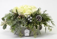 WINTER ROSE TABLE CENTRE. White roses are encircled by holy, snow covered pine cones and elegant Christmas greens. #christmas #flowers #festive #holidayseason #homedecor #decor #decorideas #floral #florists #floristlife #christmasdecoration #decorations #christmastree #xmas #westvan #westvancouver #vancouver #traditional #modern #classy #unique #unusual #christmastrees