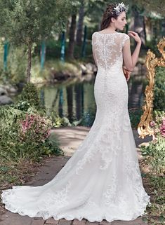 Elaborate patterned lace adorns this breathtaking tulle fit and flare wedding dress, complete with stunning illusion sweetheart neckline and illusion back. Finished with covered button over zipper closure. Tulle veil sold separately. Mercedes by Maggie Sottero
