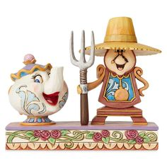 Mrs. Potts and Cogsworth strike a pose inspired by the iconic American Gothic painting. The two characters from Disney's Beauty and the Beast are handcrafted and hand-painted in exquisite detail in this stone resin figure by Jim Shore.