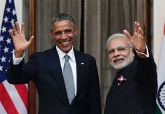 President Barack Obama (L) shakes hands with India's Prime Minister Narendra Modi in the pouring rain as he arrives to attend the Republic Day parade in New Delhi January 2015